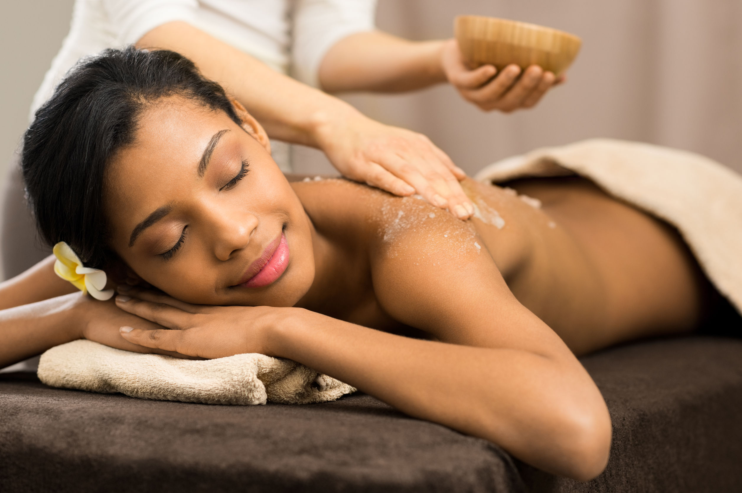 36953086 - spa therapist applying scrub salt on young woman back at salon  spa